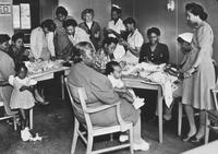 African American women and children in an office with a USO sign, ca. 1942-1946