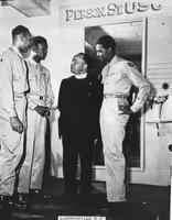 African American servicemen with Priest at USO Club entrance, Fayetteville, North Carolina, ca. 1942 - 1946