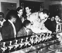 African American serviceman (boxer Joe Louis?) signing autograph for children at a soda fountain, ca. 1942 - 1946