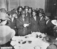 African American servicewomen at a table looking on as one woman reads a card, Des Moines, Iowa, ca. 1942 - 1946