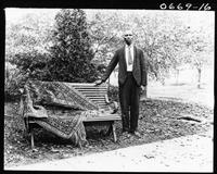 African American man standing beside a bench